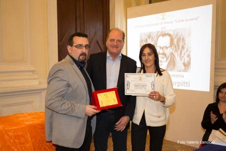 Il Presidente del Premio Lorenzo Spurio e la Presidente di Giuria Susanna Polimanti consegnano il Premio alla Memoria di Pasquale Scarpitti, ritirato dal figlio Gaetano Scarpitti